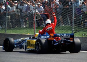 Alesi gets a taxi ride back to the pits on the back of Schumacher's Benneton.